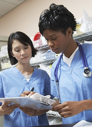 Female doctor and nurse in hospital doing paperwork